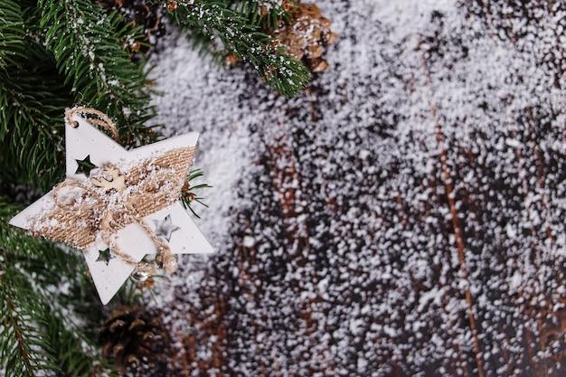 Fundo do conceito de natal, decoração artesanal de estrelas e árvores de natal verdes em uma mesa de madeira, tracejada pela neve branca