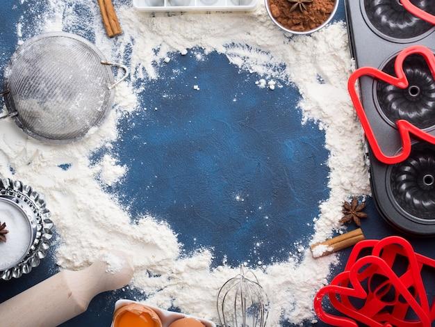 Fundo do conceito do cozimento do quadro da farinha na obscuridade - azul com acessórios das ferramentas e açúcar doce dos ingredientes da torta da cookie do bolo do alimento, ovos, cacau, canela. vista superior plana leigos fazendo conceito de massa