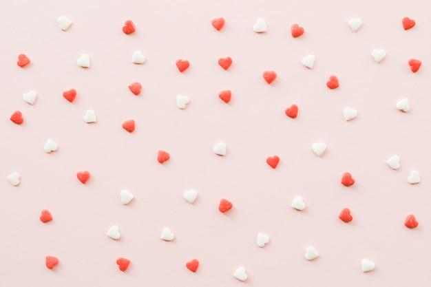 Fundo do dia de valentim com corações pequenos vermelhos e brancos no contexto cor-de-rosa.