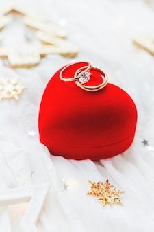 Fundo do feriado do natal e do ano novo com decorações e alianças de casamento na caixa do coração do presente.