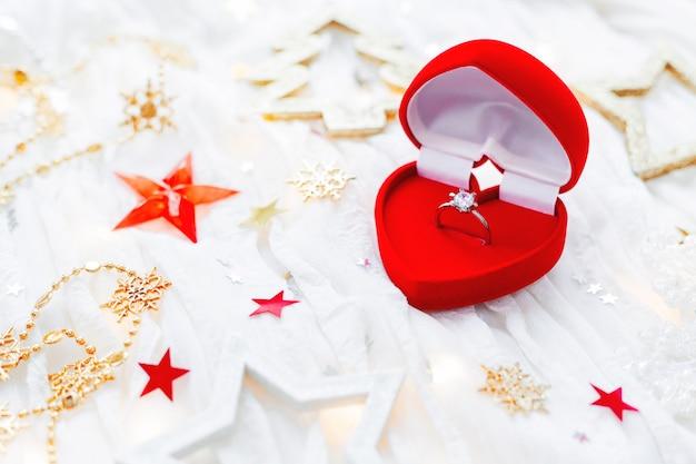 Fundo do feriado do natal e do ano novo com decorações e anel dourado do acoplamento com o diamante na caixa do coração do presente. cartão de dia dos namorados.