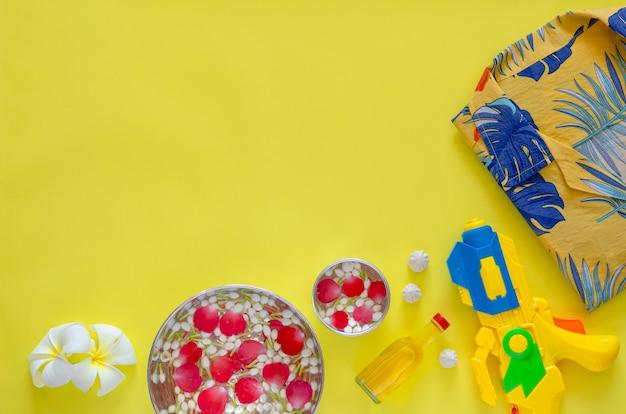 Fundo do festival songkran com flores e água perfumada para dar bênçãos e acessórios para brincar de água