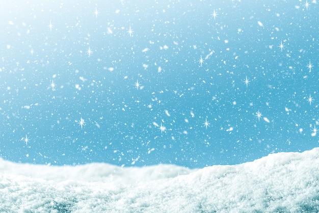 Fundo do inverno com neve e brilho na cor azul do inclinação.