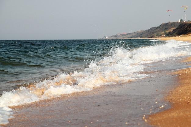 Fundo do mar tempestuoso. ondas e salpicos. praia de areia.