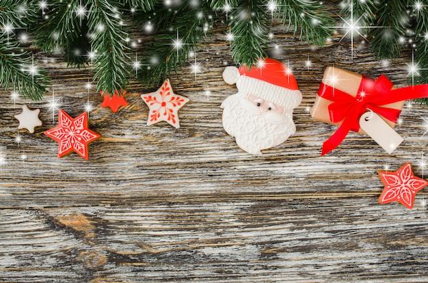 Fundo do natal com árvore de abeto, pão-de-espécie santa e presente.