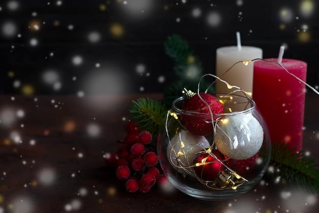Fundo do natal com decoração, velas, luz e as bolas festivas no frasco.