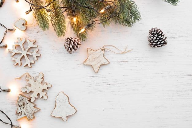 Fundo do natal - folhas do abeto e elementos rústicos que decoram na tabela de madeira branca.