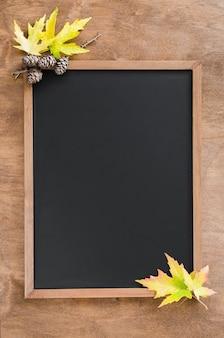 Fundo do outono com folhas e cones da queda na tabela de madeira.