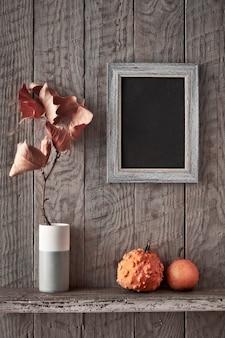Fundo do outono com quadro de quadro-negro na parede de madeira rústica, abóboras decorativas laranja e galho seco plátano em vaso, cópia-espaço