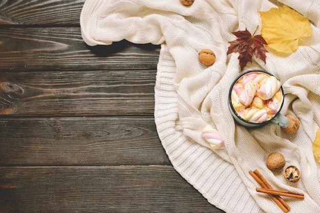 Fundo do outono feito das folhas secadas da queda, caneca de cacau com marshmallows, porcas, canela, manta, maçãs. vista superior em madeira marrom