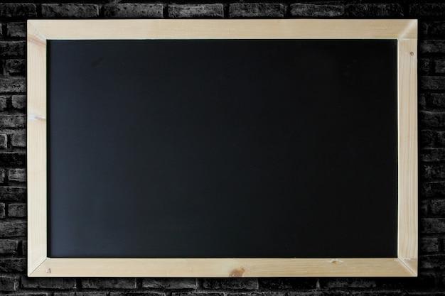 Fundo do quadro-negro e moldura de madeira no fundo da parede de tijolo.