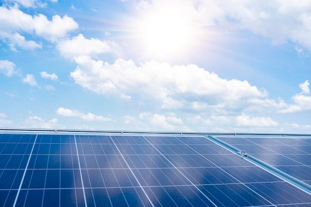 Fundo dos módulos fotovoltaicos da célula solar para a energia renovável com céu azul.