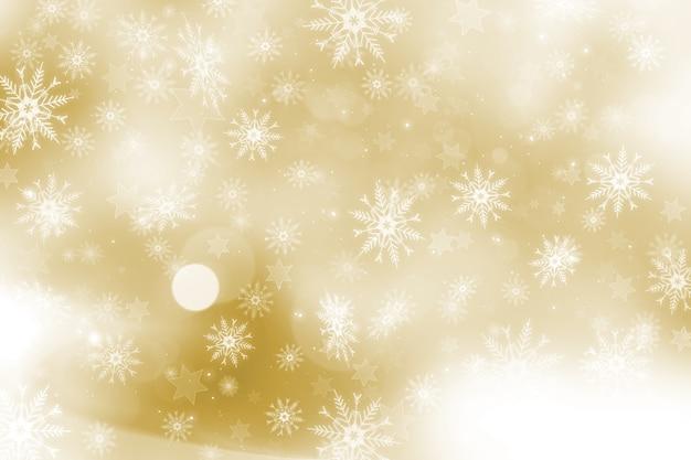 Fundo dourado de natal com flocos de neve e design de estrelas