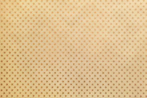 Fundo dourado de papel de folha de metal com um padrão de estrelas