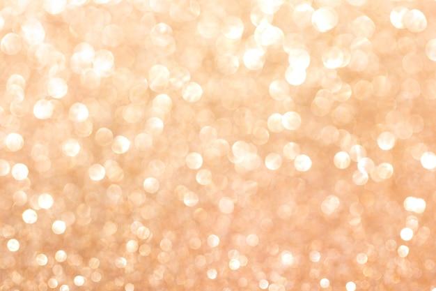 Fundo dourado glitter turva. textura cintilante e brilhante para férias de natal e ano novo ou decoração de papel de parede sazonal