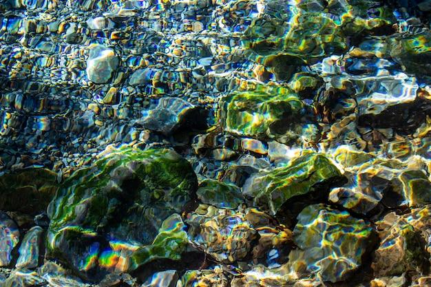 Fundo e textura abstratos de pedras e de seixos coloridos sob a água no rio.
