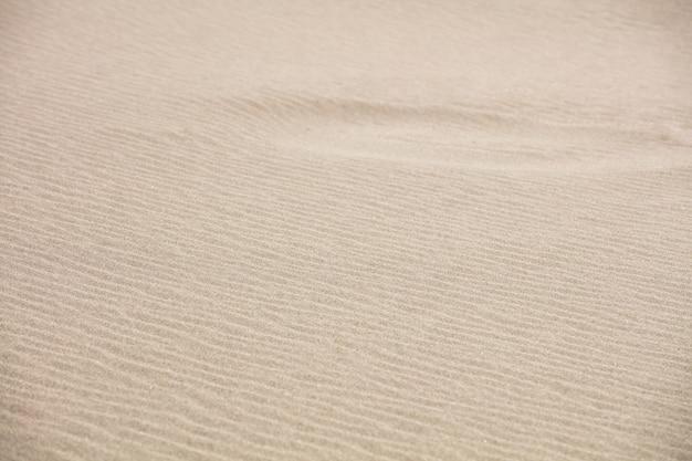 Fundo e textura da areia em uma praia no verão