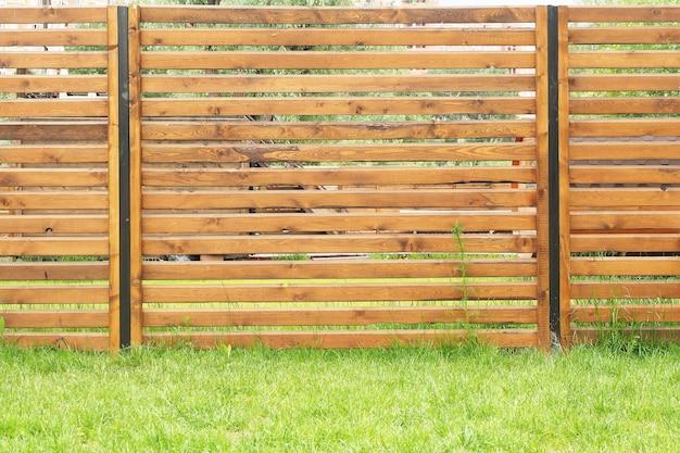 Fundo e textura da cerca das pranchas de madeira cobertas com a mancha de madeira e o gramado verde.