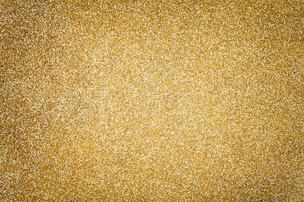 Fundo efervescente dourado das lantejoulas pequenas, close up. pano de fundo brilhante.