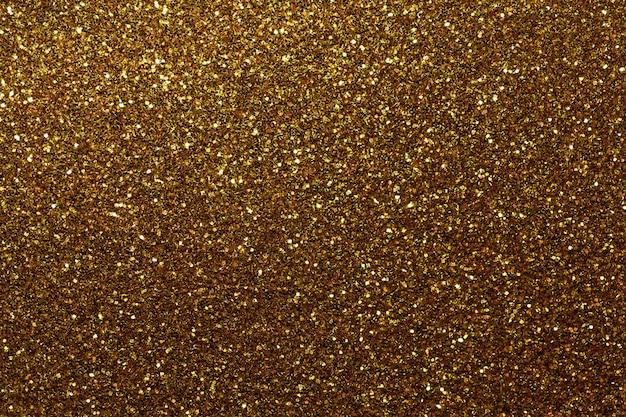 Fundo efervescente dourado escuro das lantejoulas pequenas, close up. pano de fundo brilhante.