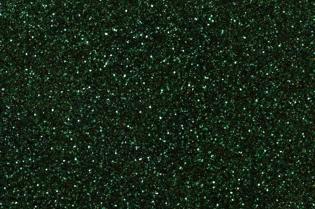 Fundo efervescente verde escuro das lantejoulas pequenas, close up. pano de fundo brilhante.