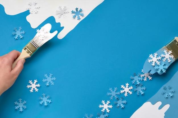 Fundo em azul e branco com pincéis carregados com flocos de neve de papel, cópia-espaço