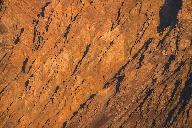 Fundo ensolarado da natureza das montanhas rochosas na luz solar. textura de montanha natural vívida de grandes rochas ásperas. quadro completo da superfície irregular gigante brilhante. close-up de montanha rochosa. avião de pedras brilhantes na sunset.