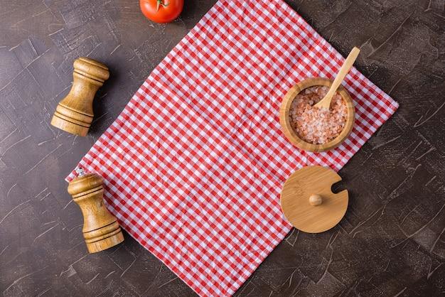 Fundo escuro com um guardanapo vermelho do serviço, sal cor-de-rosa e abanador da pimenta com abanador de sal.
