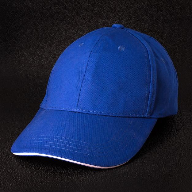 Fundo escuro de boné azul. modelo de boné de beisebol em vista lateral.