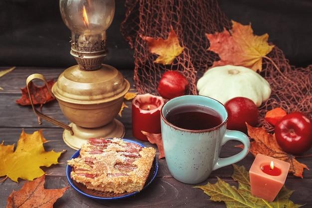 Fundo escuro de halloween com abóbora, maçãs, folhas de outono, lâmpada, torta, bebida vermelha e velas