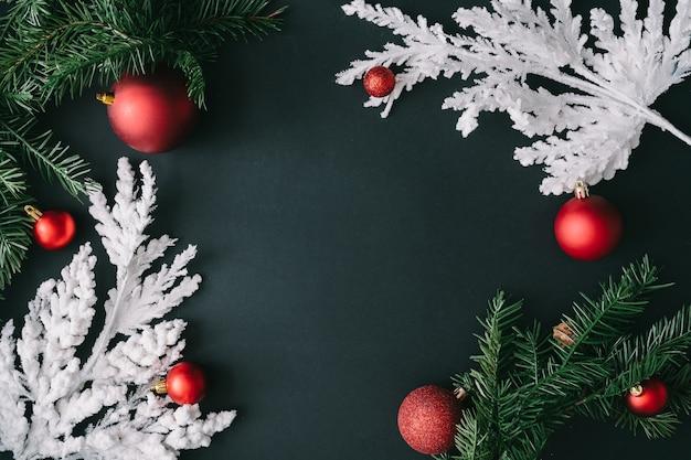 Fundo escuro de mesa de natal com galhos de árvores de natal branco e decoração de bugiganga vermelha. composição da borda. estilo liso leigo. cartão de ano novo.