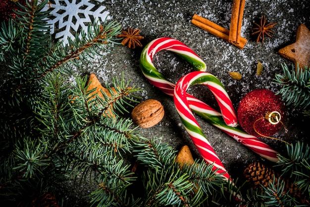 Fundo escuro de natal com galhos de árvores de natal, pinhas, doces de cana, presentes, bolas de natal