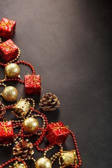 Fundo escuro de natal ou ano novo com enfeites vermelhos e dourados para a árvore de natal com espaço livre. vista de cima. espírito de natal.