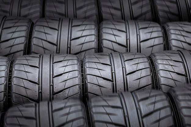 Fundo escuro de novos pneus esportivos com piso de chuva.