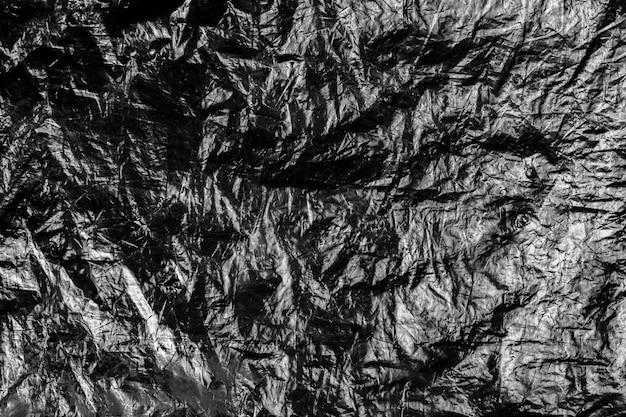 Fundo escuro de plástico amassado grunge