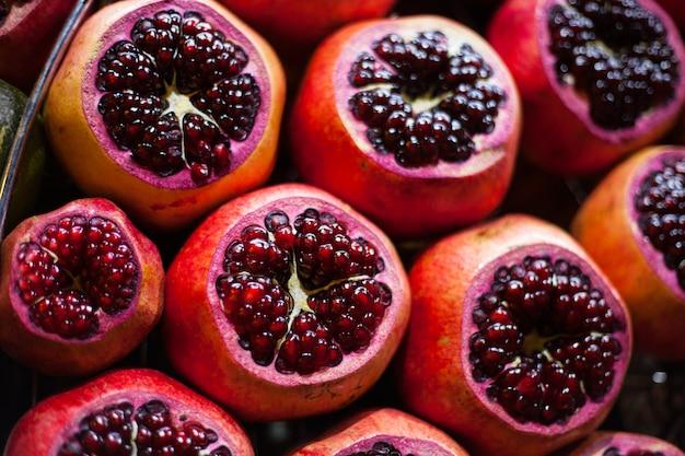 Fundo escuro de romã vermelha fresca. carga de romãs. conceito de fundo de frutas chave baixa.
