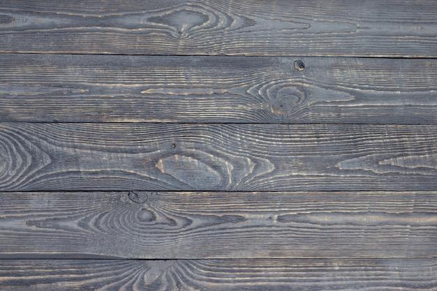 Fundo escuro de tábuas de textura de madeira com resíduos de tinta. horizontal.
