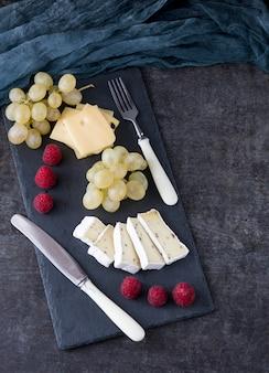 Fundo escuro e uma placa de pedra, framboesa, uvas e queijo