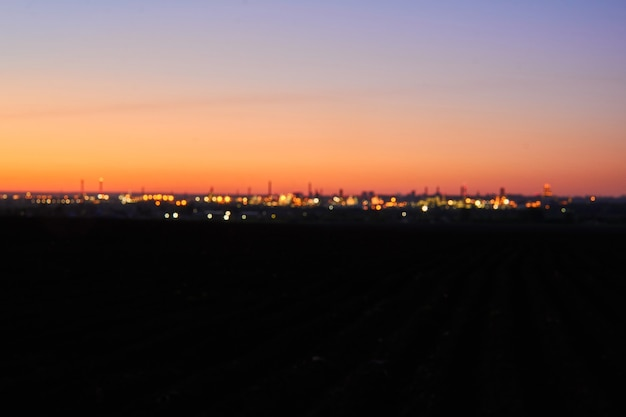 Fundo especialmente desfocado, uma cidade distante à noite em terra escura
