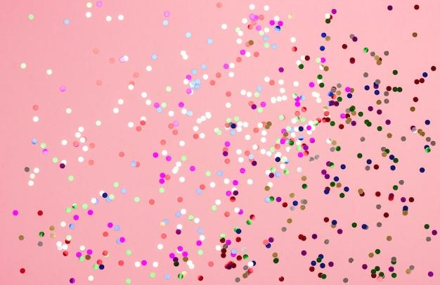 Fundo festivo bonito do rosa pastel com confetes metálicos vermelhos.