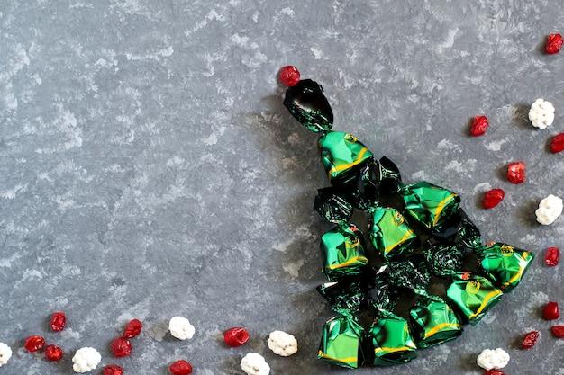Fundo festivo com árvore de chocolates de natal em embalagens de doces verdes brilhantes e frutas cristalizadas