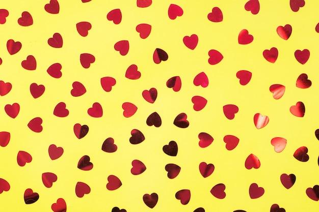 Fundo festivo com corações de confetes vermelhos em amarelo. close-up vista superior do conceito de dia dos namorados.
