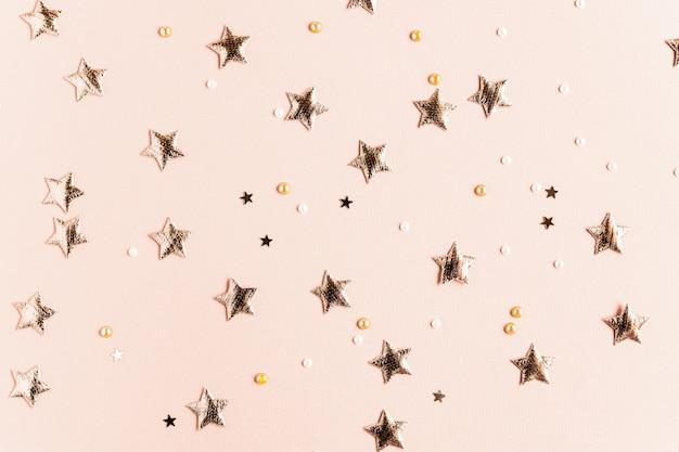 Fundo festivo com estrelas douradas e glitter em um cartão postal brilhante de fundo bege sólido