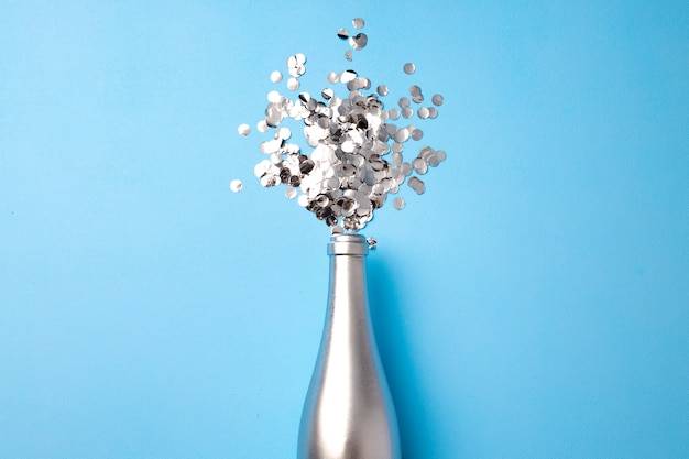 Fundo festivo com garrafa de champanhe e confetes