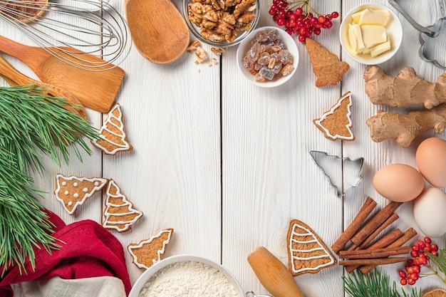 Fundo festivo com ingredientes de biscoitos de gengibre e ramos de pinheiro