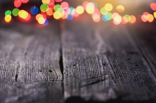 Fundo festivo com pontos de luz e bokeh em frente a uma mesa de madeira vazia