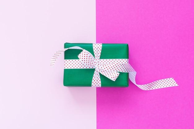 Fundo festivo com presente, caixa de presente verde com fita em bolinhas e laço rosa