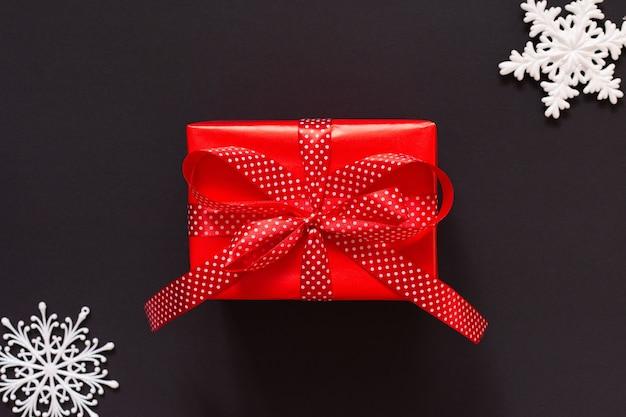 Fundo festivo com presente, caixa de presente vermelha com fita em bolinhas e arco e flocos de neve em fundo preto, conceito de sexta-feira preta, leiga plana, vista superior