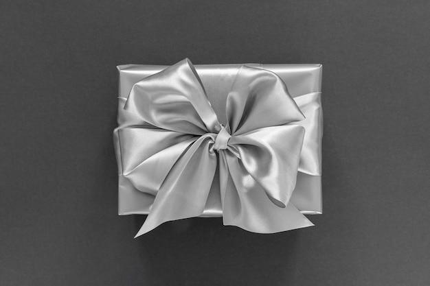 Fundo festivo com presente de prata, caixa de presente com fita de prata e arco em fundo preto, vista de cima plana