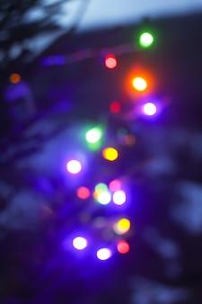 Fundo festivo de ano novo com luzes coloridas desfocadas em galhos de árvores de abeto decorados ao ar livre.